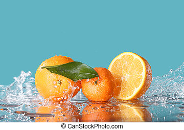 fresh orange with water splash on green background