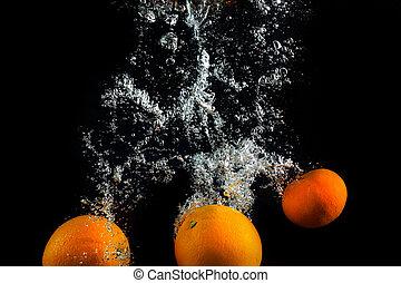 Fresh oranges in water