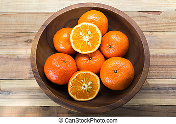 Fresh oranges in wooden bowl. On a wooden background.