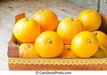 Fresh oranges in wooden box.