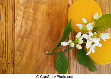 Fresh oranges with leaves and orange tree flowers on olive wood