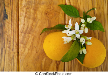 Fresh oranges with leaves and orange tree flowers on olive wood