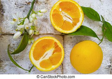Fresh oranges with leaves and orange tree flowers on rustic wood
