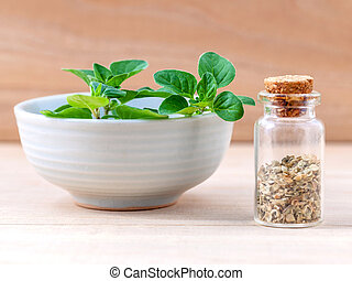 Fresh oregano and oregano dried in a the bottle with shallow depth of field setup on wooden background .