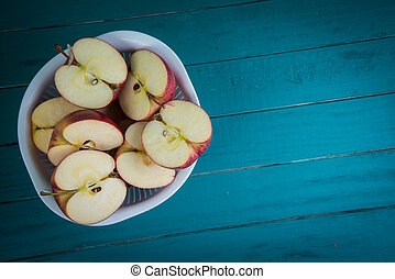 fresh organic apples halves on wooden kitchen table with...