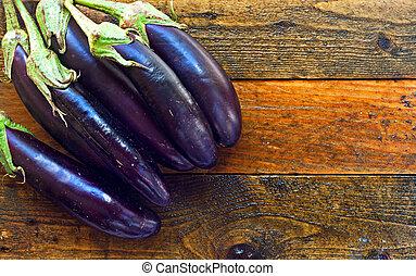 Fresh organic aubergines on rustic wooden table