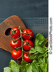 Fresh organic basil with cherry tomatoes on a wooden board as a healthy food