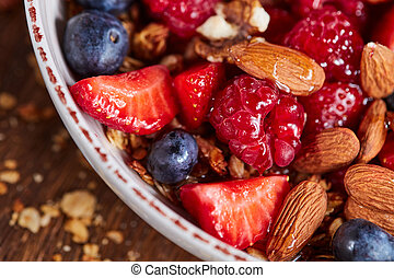 Fresh organic berries, almonds, granola, honey in a bowl - ingredients for healthy natural dietary eating. Top view.