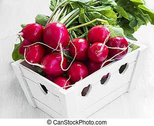 Fresh organic bunch of radishes in wooden crate