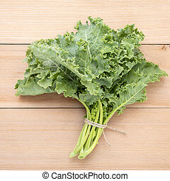 Fresh organic curly kale leaves flat lay on a wooden table ...