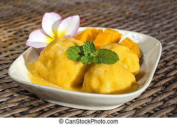 Fresh organic mango ice cream sorbet with mint leaves on table, close up. Thailand