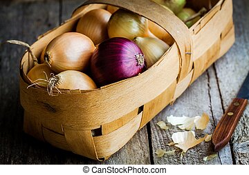 Fresh organic onions in a basket on a wooden background