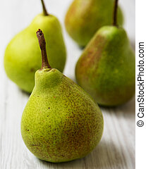 Fresh organic pears on a white wooden background, side view. Close-up.