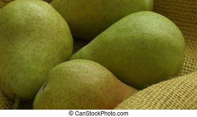 Fresh organic pears on yellow sacking. Pear autumn harvest. Juicy flavorful pears of rustic background.