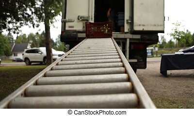 A local grower prepares to sell crops at a farmers market, unloading trays of fresh produce from the back of a truck, sliding down a ramp onto display