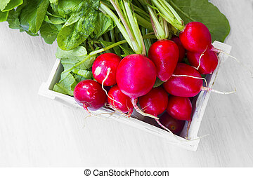 Fresh organic radish bunch in wooden crate