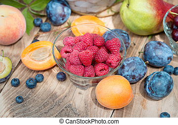 Fresh organic raspberries and other seasonal fruits - healthy eating