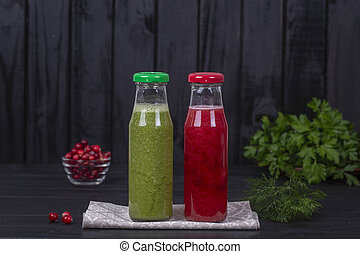 Fresh organic red and green two smoothie in glass bottle on black wooden table, closeup. Refreshing summer fruit drink. The concept of healthy eating. Cranberry and raspberry smoothie