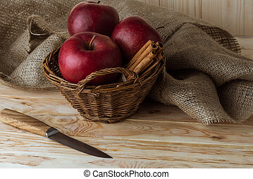 fresh organic red apples and cinnamon sticks in wicker basket with knife on wooden tabletop