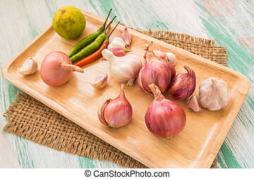 Fresh organic red onion in wooden plate