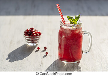 Fresh organic red smoothie in glass mug on white table, close up. Refreshing summer fruit drink. The concept of healthy eating. Cranberry and raspberry smoothie
