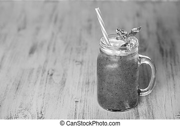 Fresh organic smoothie in glass mug on wooden table. Refreshing summer fruit drink. The concept of healthy eating. Copy space, black and white