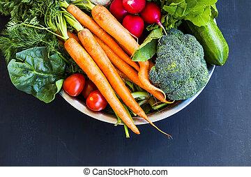 Fresh organic vegetables bowl with carrots, cauliflower, broccoli, tomatoes, mushrooms, radishes on wooden board