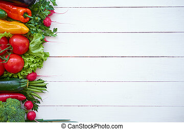 Fresh organic vegetables on white wooden boards background, top view.