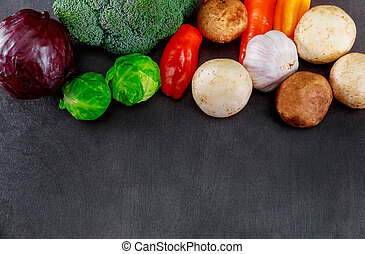 Fresh organic vegetables placed of dark wooden background vegetables included in the composition from free text space.