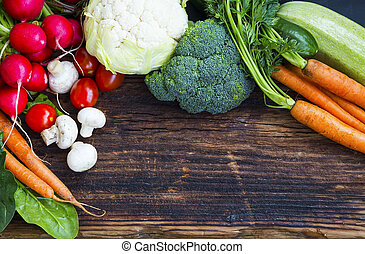 Fresh organic vegetables with carrots, cauliflower, broccoli, tomatoes, mushrooms, radishes on wooden board