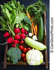 Fresh organic vegetables with carrots, cauliflower, broccoli, tomatoes, mushrooms, radishes on wooden tray
