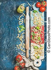 Fresh pasta casarecce, tomatoes, basil, olive oil on colorful board