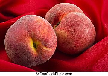 fresh peach fruits on red velvet