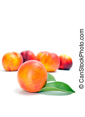 fresh peach fruits with green leaves isolated on white background