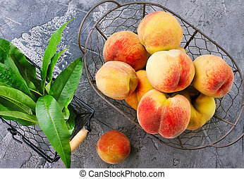 peach - fresh peach in metal basket and on a table