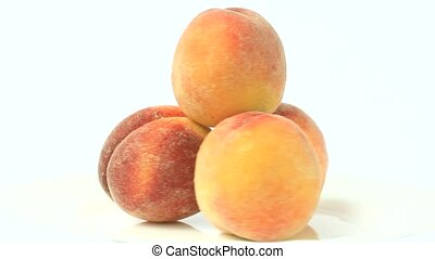 Fresh peaches are rotated on a white backgrounds