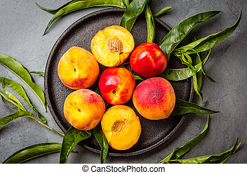 Fresh peaches on black plate, gray slate background. top view