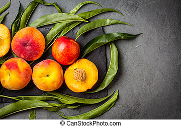 Fresh peaches on black stone plate, gray slate background