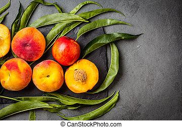 Fresh peaches on black stone plate, gray slate background
