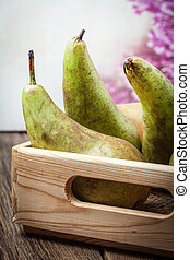 Fresh pears in a box on wooden background.