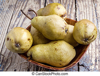 Fresh pears in a wooden bowl