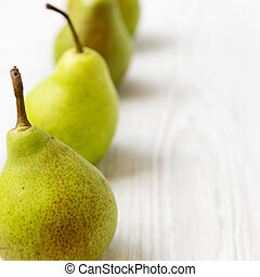 Fresh pears on a white wooden background, side view. Close-up.