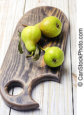 Fresh pears on brown wooden cutting board.