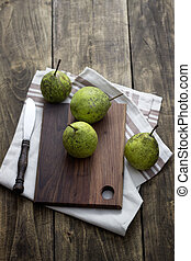 fresh pears on wooden cutting board