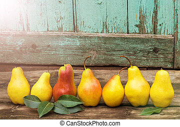fresh pears with leaves on the dark rustic wooden table