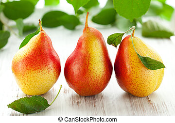 pears - fresh pears with leaves  on the white wooden  table
