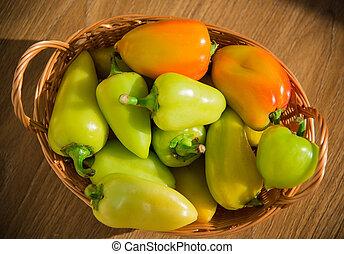Fresh pepper in a wicker basket on a wooden table.