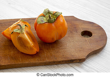 Fresh persimmon on a chopping board on white wooden background, side view. Close-up.
