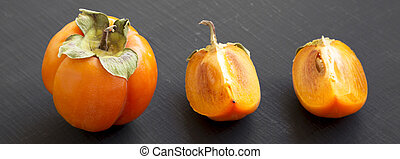 Fresh persimmon on black background, side view. Closeup.