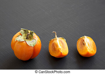Fresh persimmon on black surface, side view. Close-up. Copy space.